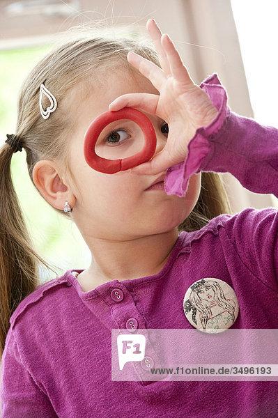 Mädchen schaut durch einen Ring aus Knete  Porträt