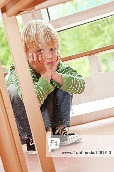 Junge hockt neben einem Tisch und stützt seinen Kopf in den Händen  Flachwinkelansicht Junge hockt neben einem Tisch und stützt seinen Kopf in den Händen, Flachwinkelansicht