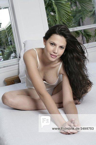 Portrait einer jungen Frau in Unterwäsche sitzen auf dem Bett