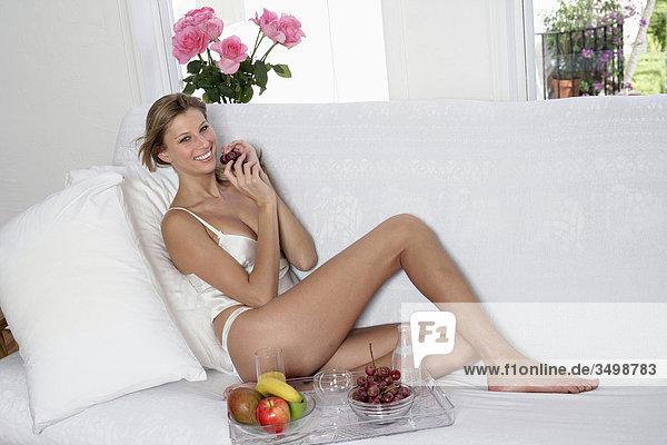 Portrait einer jungen Frau in Unterwäsche sitzen auf dem Bett mit eine Schüssel mit Früchten