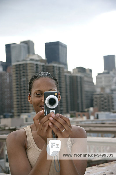 Woman taking picture with a camera  skyline of New York in the background  USA