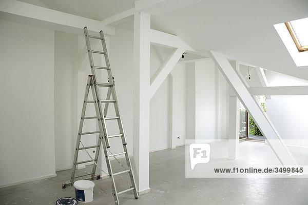 Leiter und Farbeimer in einer Dachgeschosswohnung