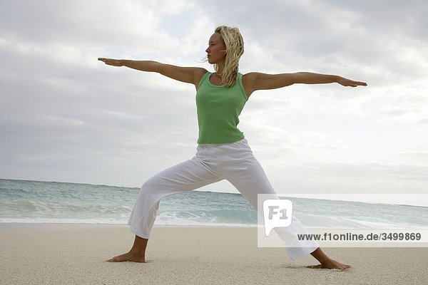 Junge Frau praktiziert Yoga am Strand  Flachwinkelansicht