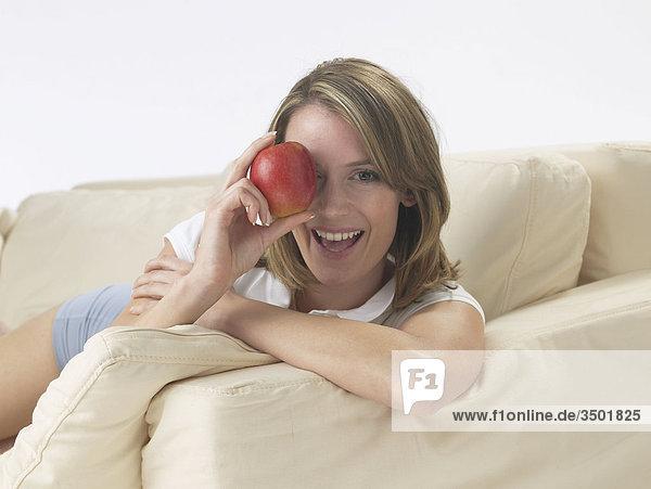 Frau hält sich Apfel vor das Auge