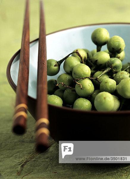 Grüne Beeren in Schale mit Stäbchen