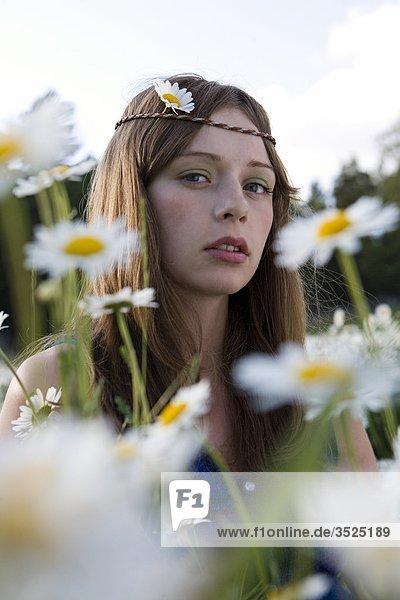 Portrait einer jungen Frau mit Daisies im Vordergrund