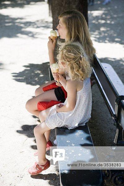 Mädchen auf Bank sitzen und Eis essen