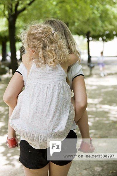Mädchen mit Schwester auf Rückseite
