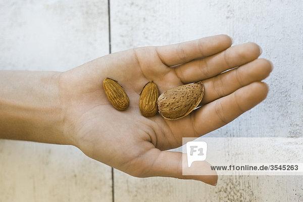 Hand hält Mandeln