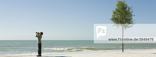 Junge steht am Strand und schaut mit einem Fernglas auf das Meer.