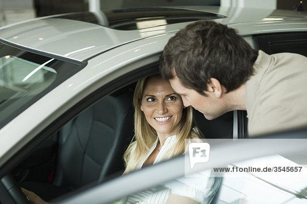 Paar beim Auschecken von Neuwagen im Autohaus