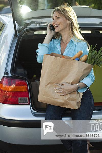 Frau sitzt in offener Heckklappe mit Einkaufstasche auf dem Schoß und telefoniert.