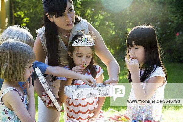 Mutter hilft Tochter offenes Geschenk bei Geburtstagsfeier