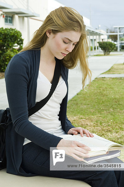 Studentinnen sitzen auf der Bank und lesen auf dem Campus.