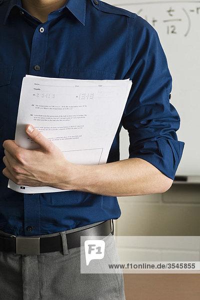 Lehrer bereitet sich auf das Verteilen von Prüfungen vor