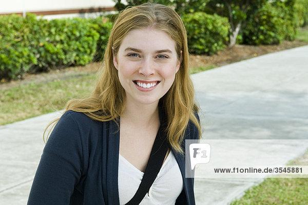 Junge Frau lächelt vor der Kamera  Porträt