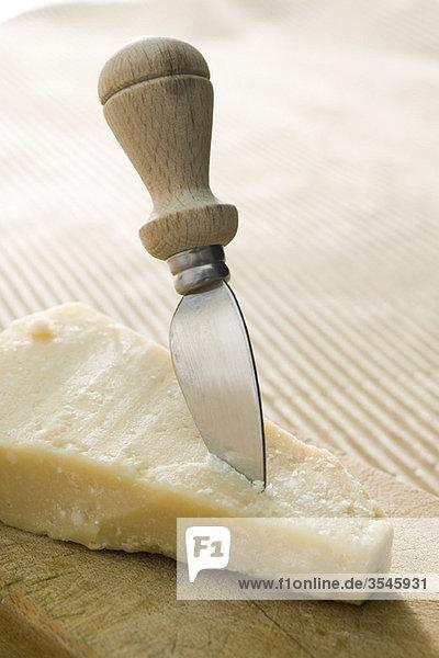 Käsemesser in einem Stück Parmaesan-Käse geklebt