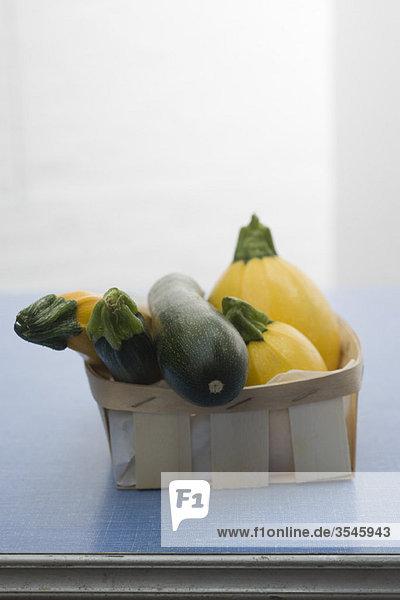 Zucchini und Goldkürbis im Korb