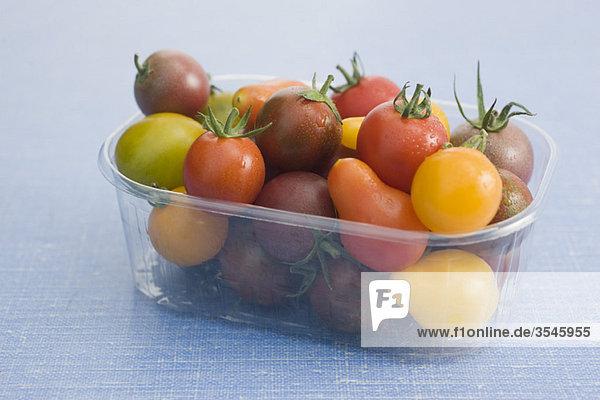 Verschiedene Kirsch- und Pflaumentomaten im Kunststoffbehälter