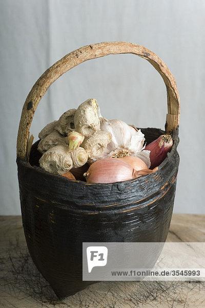 Korb mit Zwiebeln  Knoblauch und Ingwerwurzel