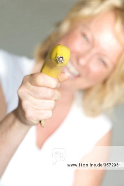 Reife Frau zielt mit einer Banane