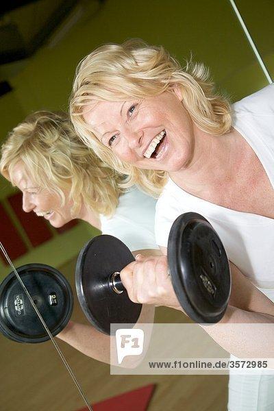Reife Frau macht Gewichtstraining im Fitness-Studio