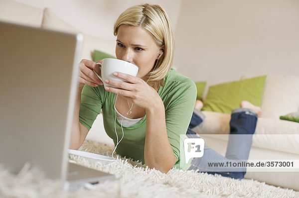 Junge Frau liegt auf einem Teppich mit Kaffeetasse  Ohrstöpseln und Laptop