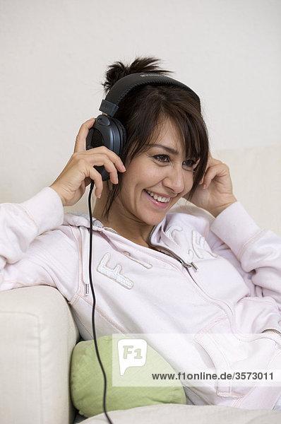 Fröhliche Frau im Wohnzimmer mit Kopfhörern