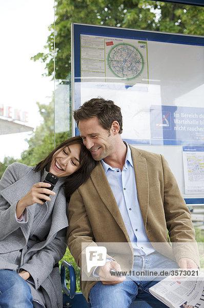 Fröhliches Paar an Straßenbahn-Haltestelle mit Zeitung und Handy