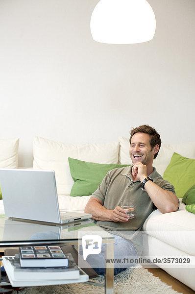 Fröhlicher Mann im Wohnzimmer schaut auf Laptop