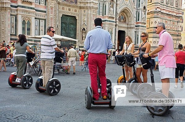 People riding segways in front of the cathedral  Florence  Tuscany  Italy