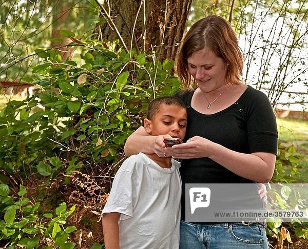 This young modern Caucasian mother is text messaging with her cute bi-racial son in a family moment together of learning technology Background is intentionally blurred to emphasize subject