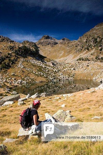 mountaineer woman near a small lake Colomers glaciar cirque Aran Valley Pyrenees mountain range Lerida province Catalonia  Spain  Europe