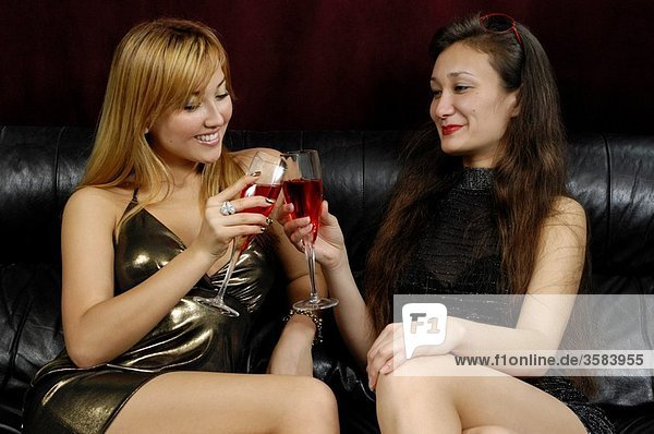 Two attractive smiling women sitting on a couch with red wine