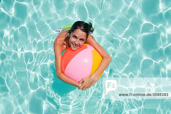 Junge Frau im Schwimmbad mit Strandball