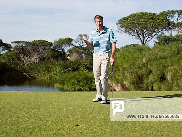 Ekstatische Mann Golf zu spielen