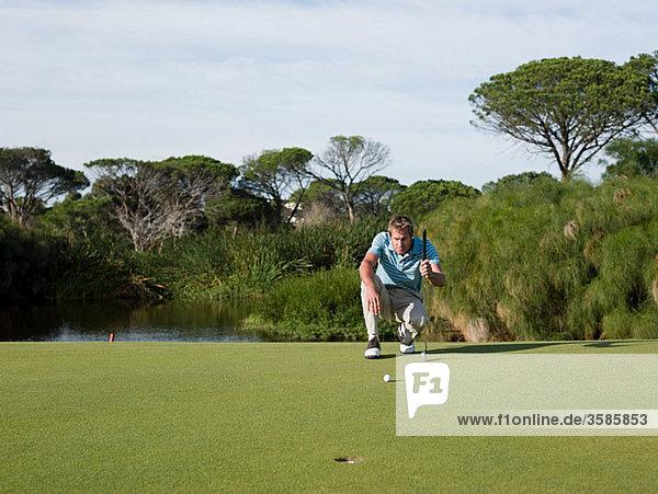 Mann spielt Golf  auf Putting Green