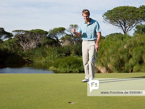 Ekstatischer Mann beim Golfen