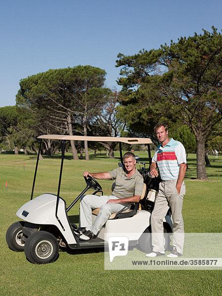 Zwei reife Männer im Golfwagen auf dem Golfplatz