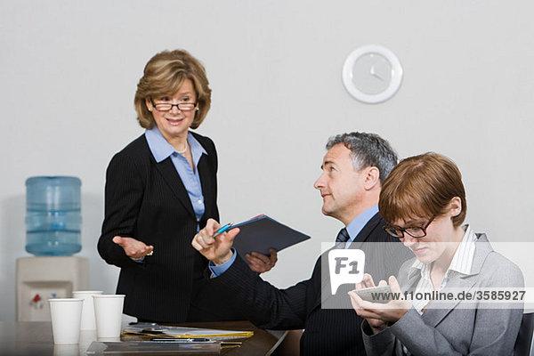 Geschäftsfrau sitzt auf dem Schreibtisch und redet.