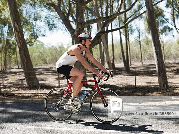 Junger Mann Radfahren im Wald