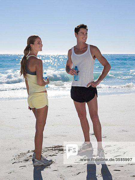 junges Paar mit Flaschen Wasser am Strand