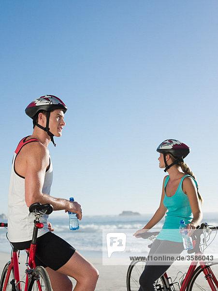 Junges Paar beim Radfahren am Strand