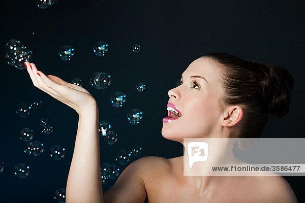 Junge brünette Frau mit schwebenden Blasen