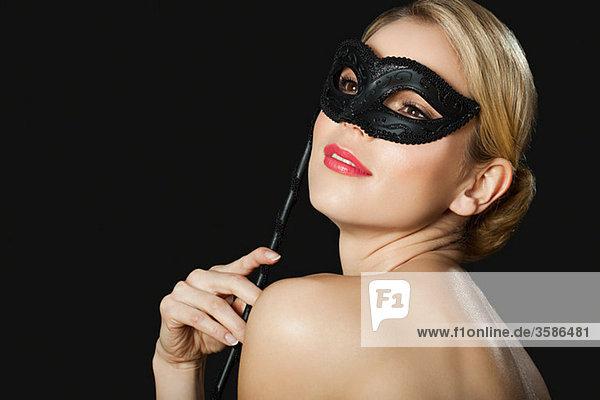 Junge blonde Frau mit schwarzer Maske