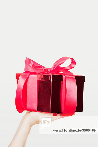 Junge Frau  die ein Geschenk anbietet