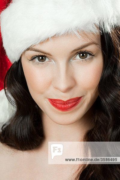Junge brünette Frau mit Weihnachtsmütze