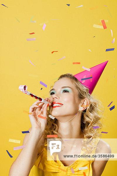 Junge Frau mit Partyhut mit Partybläser und Konfetti