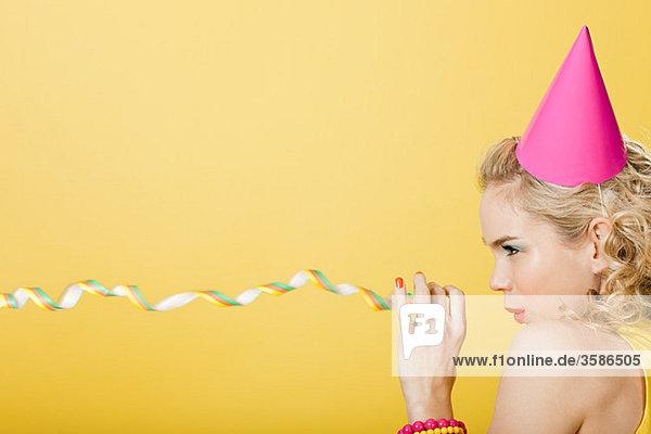 Junge Frau mit Partyhut und Party-Streamer