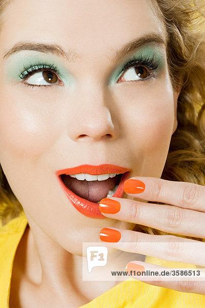 Überraschte junge blonde Frau vor gelbem Hintergrund